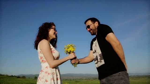 a young man giving floral bouquet to pretty girlfriend,in two frames - bunch stock videos and b-roll footage