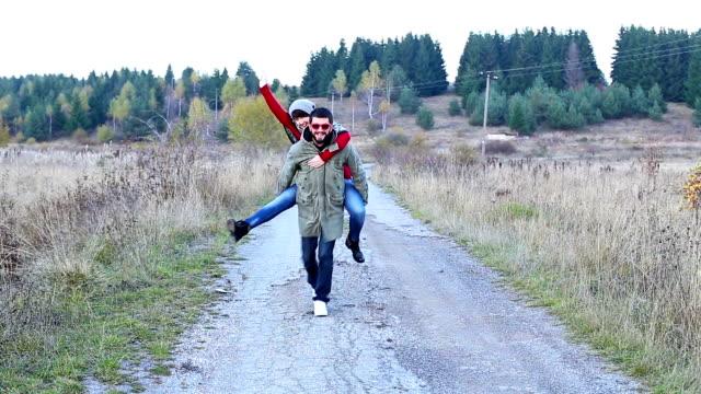 Giovane uomo dando alla sua fidanzata un piggyback giro nella natura