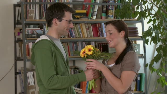ms young man giving young woman bouquet of flowers in their apartment / berlin, germany - cavalleria video stock e b–roll