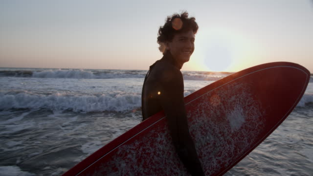 sm young man going surfing at sunset - surfing stock videos & royalty-free footage