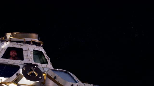 junger mann grüßt von einer raumstation im orbit - stapellauf stock-videos und b-roll-filmmaterial