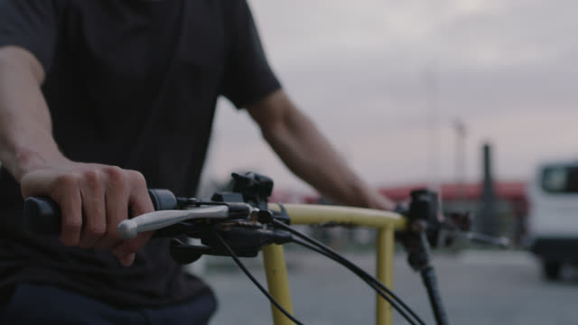 vidéos et rushes de cu slo mo. young man grips handlebars and drives bike taxi pedicab down city street. - pousse pousse