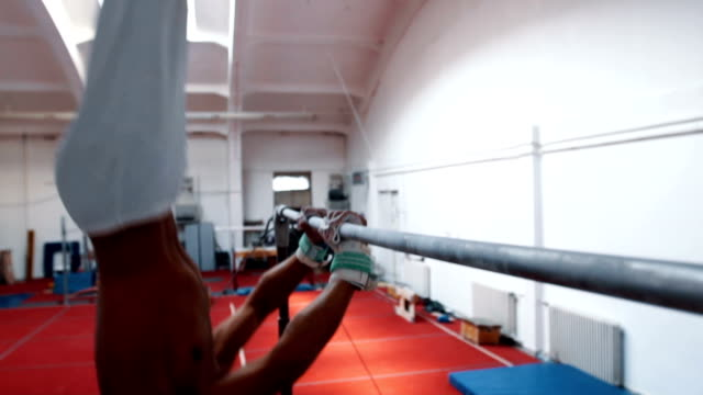 Young man gymnastics close up on horizontal bar
