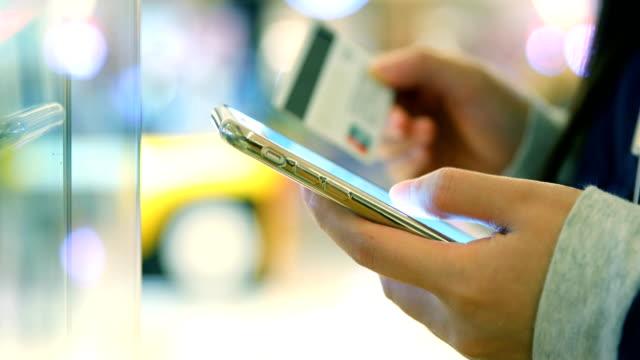 vídeos de stock, filmes e b-roll de jovem de mãos segurando um cartão de crédito e telefone - pagamento móvel