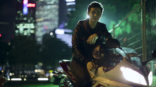 vídeos de stock e filmes b-roll de ms young man hanging out on his motorcycle at night. - capacete moto