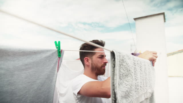 young man hanging up clothes - washing line stock videos & royalty-free footage