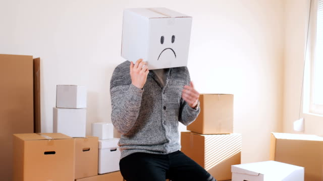 Young man have a box with sad emoticon on head