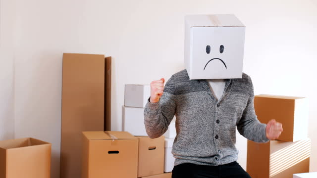 young man have a box with sad emoticon on head - moving towards stock videos & royalty-free footage