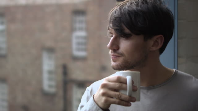 young man having a coffee - balkon stock-videos und b-roll-filmmaterial