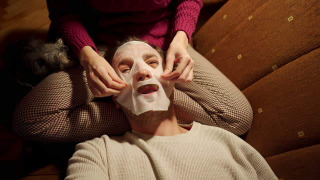 young man having a cozy time, while his girlfriend playing on his face a sheet face mask during night time - skin care stock videos & royalty-free footage
