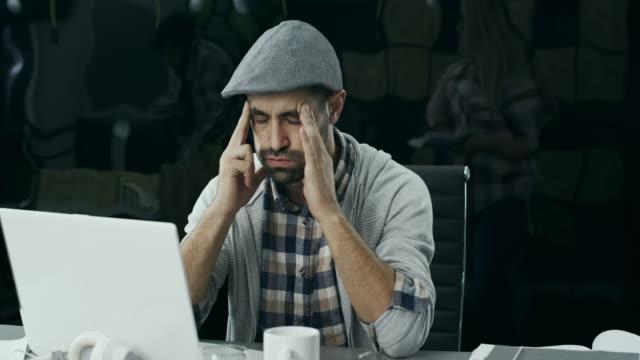 stockvideo's en b-roll-footage met jonge man met een hoofdpijn op kantoor - verkoudheid en griep