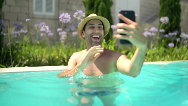 young man having a video chat on smart phone at swimming pool - photo messaging stock videos & royalty-free footage
