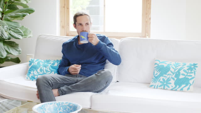 Young man having coffee on sofa at home