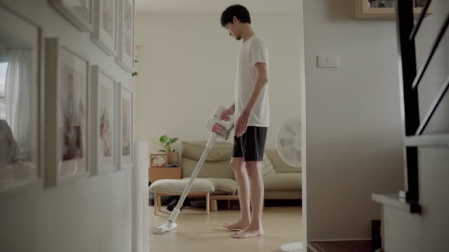 young man having fun cleaning house with vacuum cleaner living room - vacuum cleaner stock videos & royalty-free footage