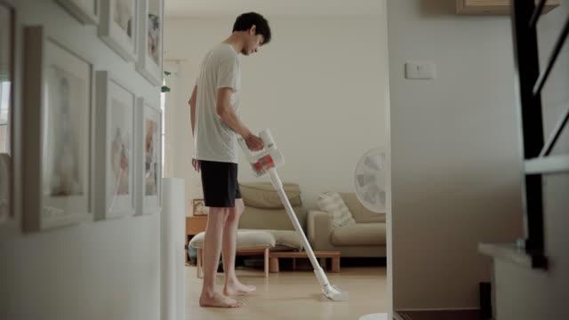 掃除機のリビングルームで家を掃除する楽しい若者 - 掃除機点の映像素材/bロール