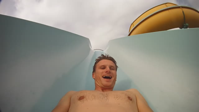 hd: young man having fun on a waterslide - water slide stock videos & royalty-free footage