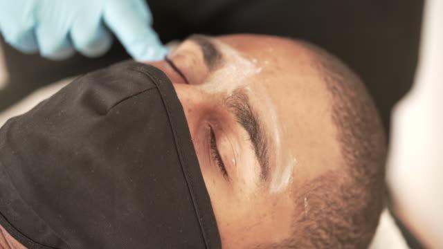 vídeos de stock e filmes b-roll de a young man having his eyebrows prepped ready for waxing as part of series - depilação