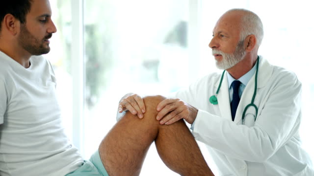 Young man having his knee examined 4k