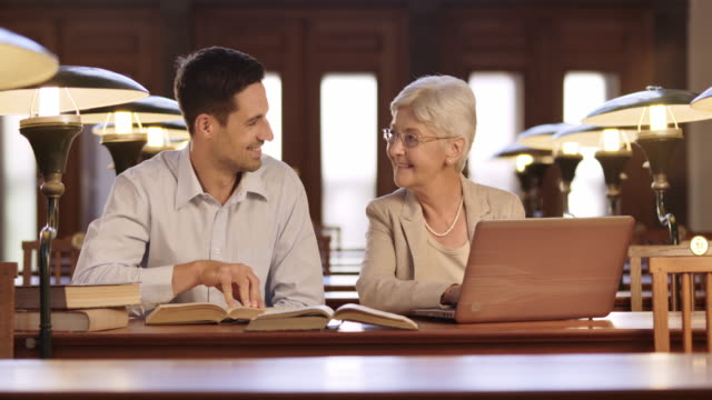 ds young man helping a senior woman learn how to use a laptop in a library - wisdom stock videos & royalty-free footage