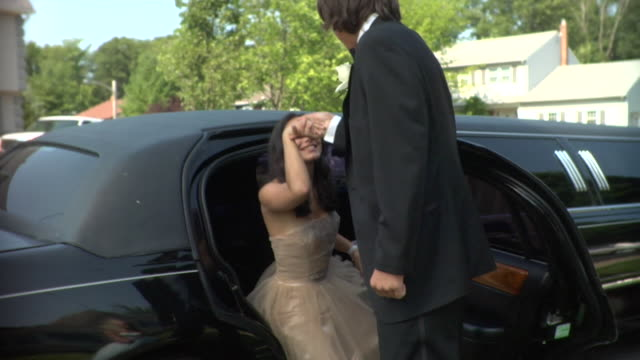 ms, young man helping girl (16-17) to get out from limo, edison, new jersey, usa - coppia di adolescenti video stock e b–roll
