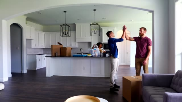 young man helps his buddy move into a new home - home ownership stock videos & royalty-free footage