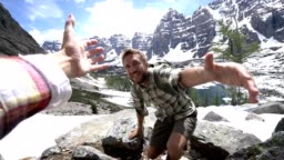 Young man hiking in the Canadian rockies, hand reach out to help