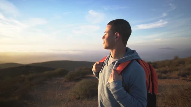 vídeos y material grabado en eventos de stock de ms young man hiking in the mountains - mirar el paisaje