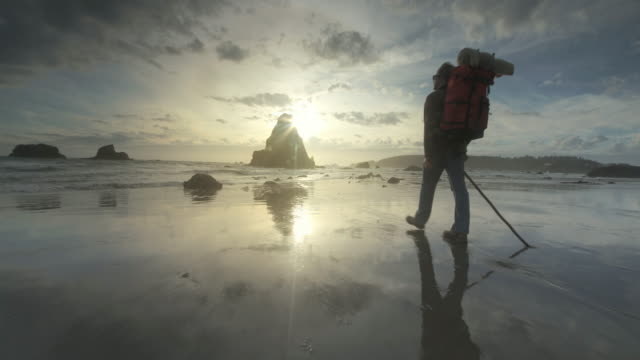Young man hiking Pacific Ocean at sunset