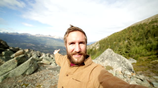 Young man hiking takes selfie portrait in mountain top