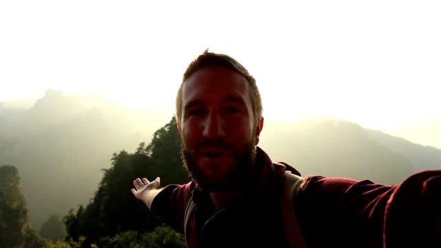 vidéos et rushes de jeune homme de randonnée portrait prend selfie - grès