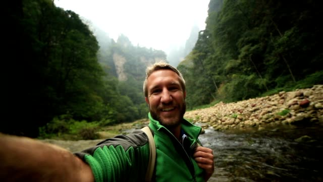 young man hiking takes smart phone selfie, china - selfie video stock e b–roll