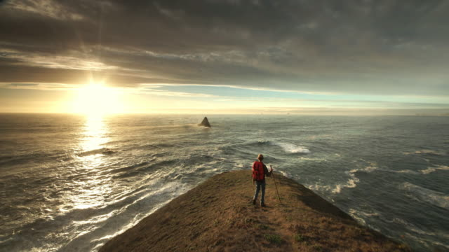 young man hiking trail overlooking pacific ocean at sunset - track imprint stock videos and b-roll footage