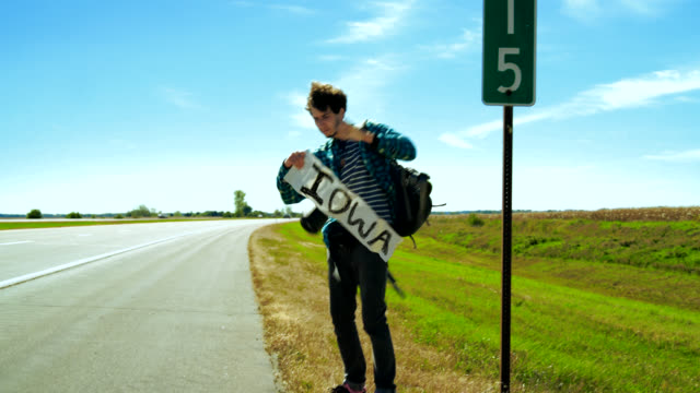Young man, hitchhiker, trying to stop the car to Iowa on the highway in the Illinois, USA.
