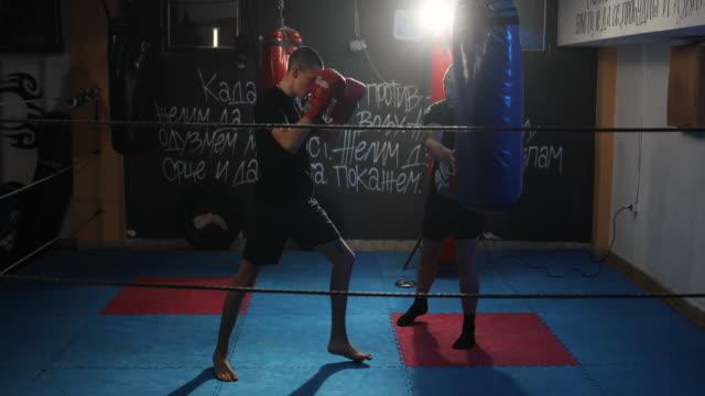 vidéos et rushes de jeune homme frappant le sac de poinçonnage sur la formation de boîte de coup de pied avec son entraîneur - 16 17 ans