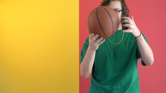 young man holding a basketball in front of colored wall - young men stock videos & royalty-free footage