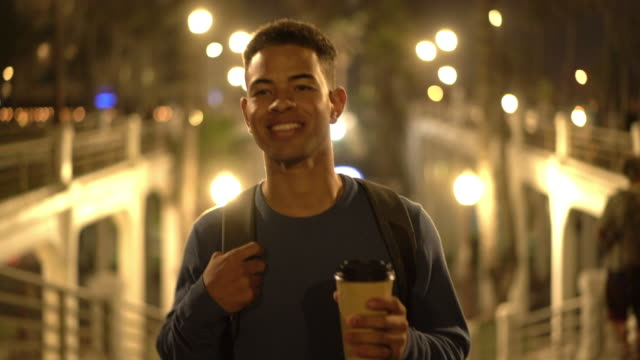 ms ts young man holding a coffee cup walking down a street at night - jumper stock videos & royalty-free footage