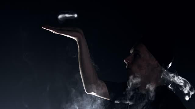vídeos y material grabado en eventos de stock de hombre slo mo joven sosteniendo un anillo de humo - truco