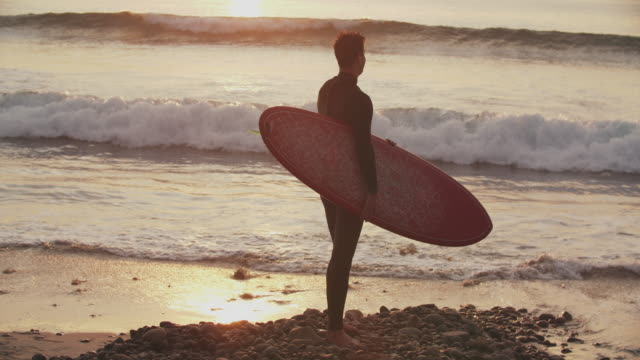 ws sm young man holding a surfboard looking at the waves at sunset - wetsuit stock videos & royalty-free footage