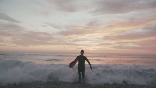 ws sm young man holding a surfboard walking out of the water - cold temperature stock videos & royalty-free footage