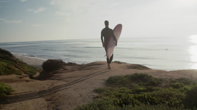 vidéos et rushes de sm ws rv young man holding a surfboard walking to the beach - cheveux courts