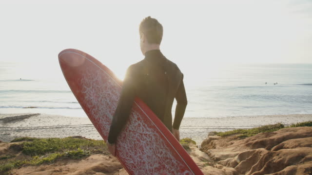 sm ms young man holding a surfboard walking to the beach - surfing stock videos & royalty-free footage