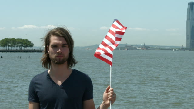 A young man holding an American flag outside in New York City in slow motion