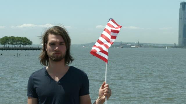 vídeos y material grabado en eventos de stock de a young man holding an american flag outside in new york city in slow motion - cabello largo