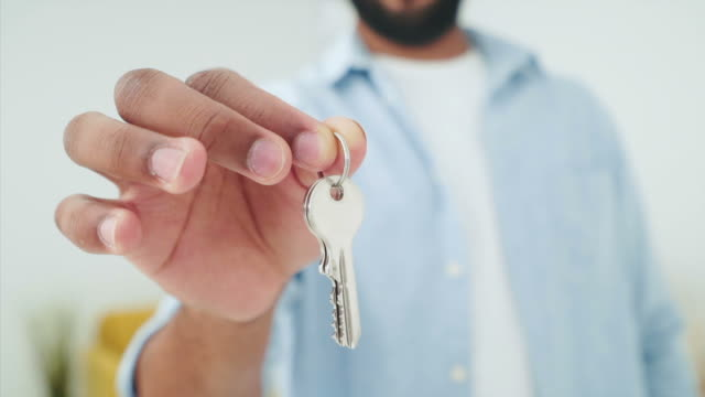 young man holding and showing home keys. - house key stock videos & royalty-free footage