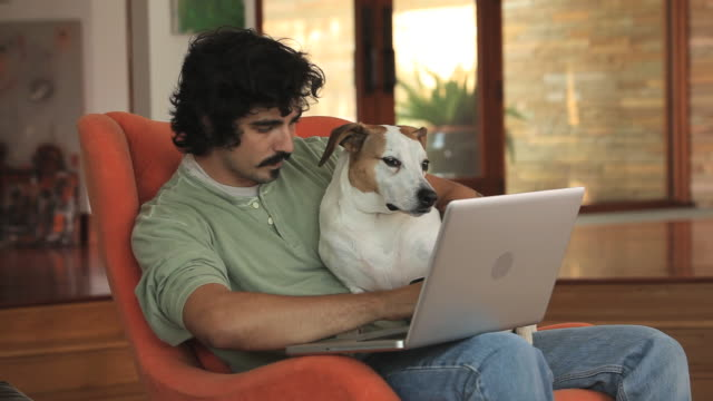 MS Young man holding credit card and using laptop with dog on lap / Richmond, Virginia, USA