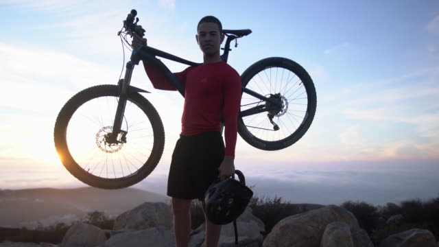 vidéos et rushes de ws young man holding his mountain bike at the top of a mountain - casque de vélo