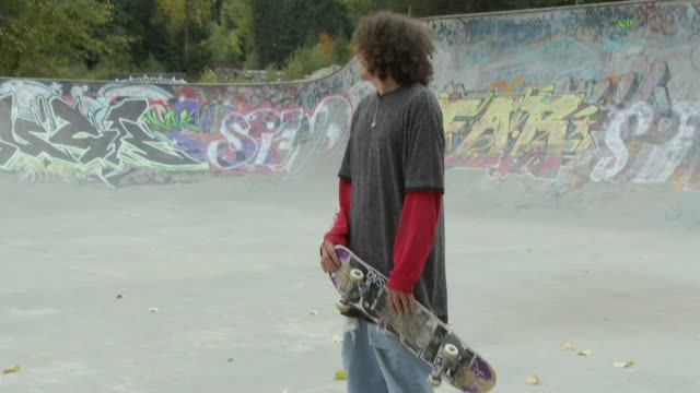 MS TU Young man holding skateboard in skatepark in front of Whistler mountain / Whistler, British Columbia, Canada