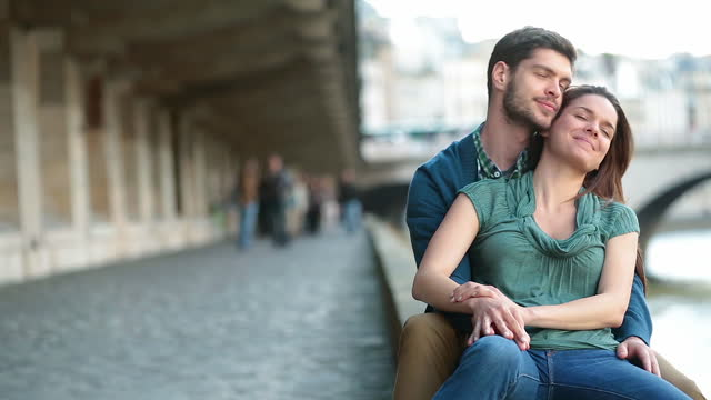 young man holds his girlfriend and kisses her forehead as they relax by the river seine in paris. - sitta bildbanksvideor och videomaterial från bakom kulisserna