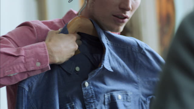 Young man holds up denim shirt and chats with shop worker in clothing store