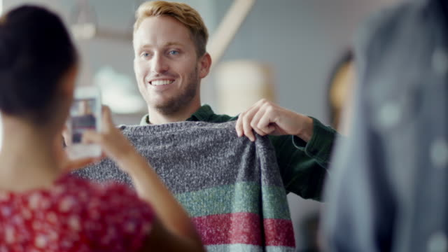 Young man holds up sweater and poses for smartphone photo in trendy clothing shop